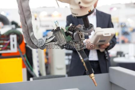 industrial welding robotic arm blurred operator