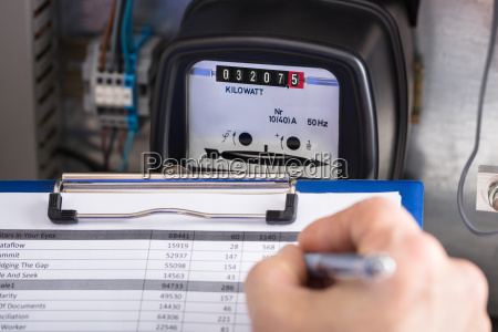 technician writing reading of meter on