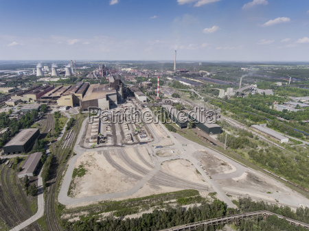 steel factory with smokestacks at sunny