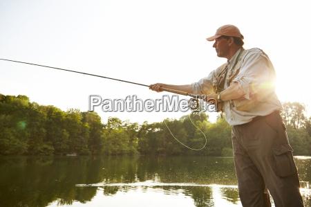 senior man fly fishing at summer