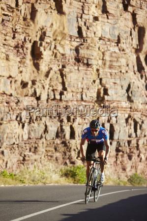 male triathlete cyclist cycling on sunny
