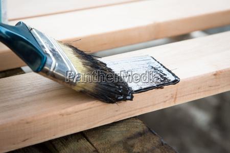 varnishing natural wood with paint brush