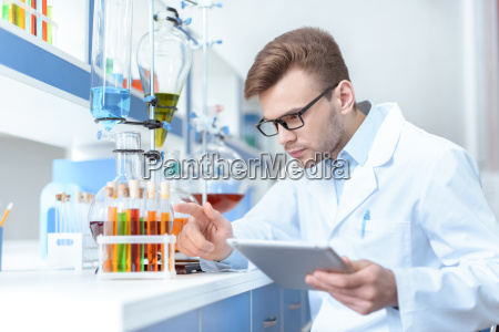 young concentrated man scientist holding digital