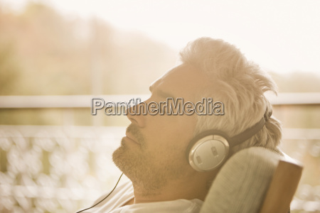 serene man with headphones listening to