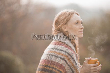 serene woman wrapped in blanket drinking