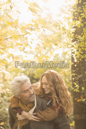 affectionate couple piggybacking in autumn woods