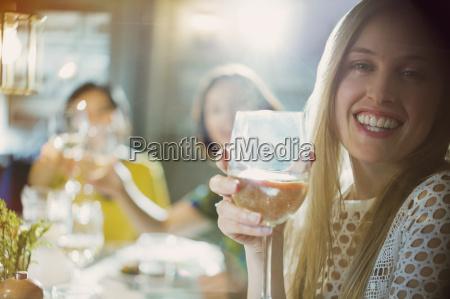 portrait smiling woman drinking white wine