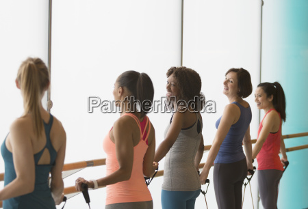 smiling women exercising with resistance bands