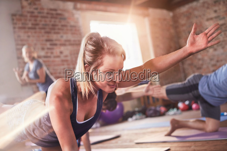 young woman doing bird dog plank