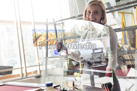 portrait smiling stained glass artist lifting