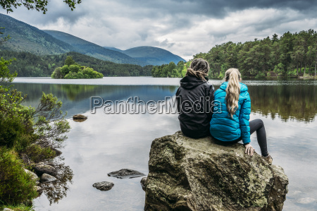 couple sitting on rock looking at