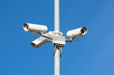 surveillance cameras against blue sky security