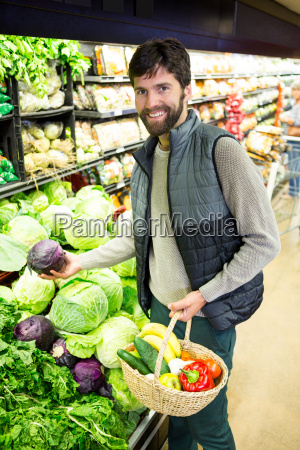 portrait of man buying vegetables in