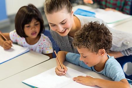 teacher helping schoolchildren to write on