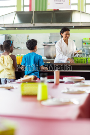 woman serving food to schoolchildren