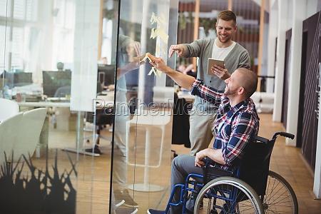 businessman assisting handicap colleague in creative