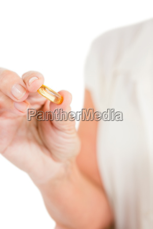 cropped image of woman showing capsule