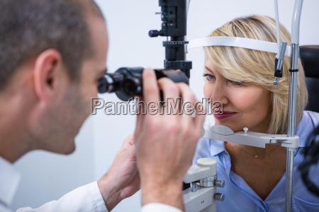 optometrist examining female patient on slit