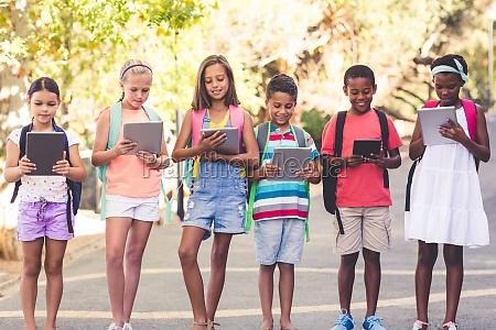 group of school kids using digital