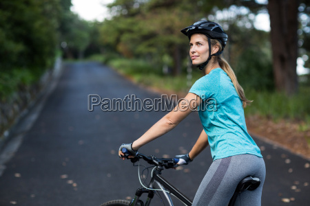 woman standing with mountain bike on
