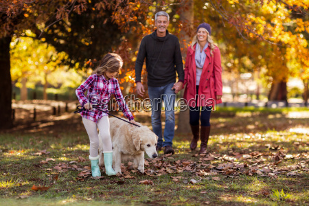 girl with dog while parents walking