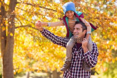 father carrying son on shoulder against