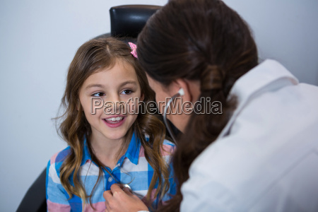 female optometrist examining young girl with