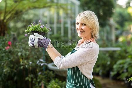 portrait of mature female gardener holding