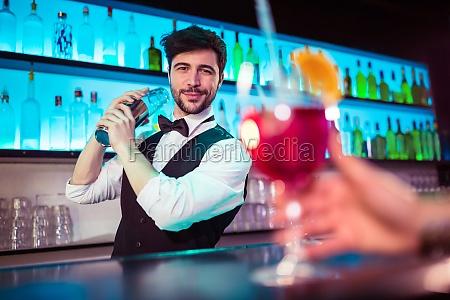 handsome barkeeper preparing cocktail at bar