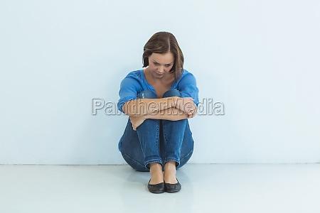 sad woman sitting against wall