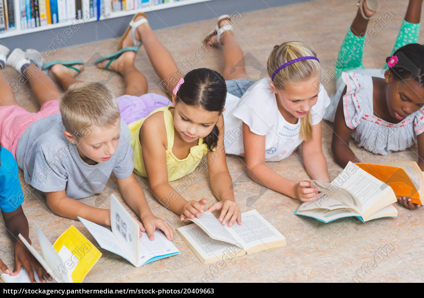 Royalty free image 20409663 - School kids lying on floor reading book in  library