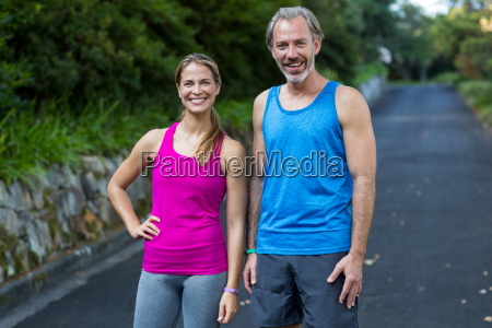athletic couple standing on road after