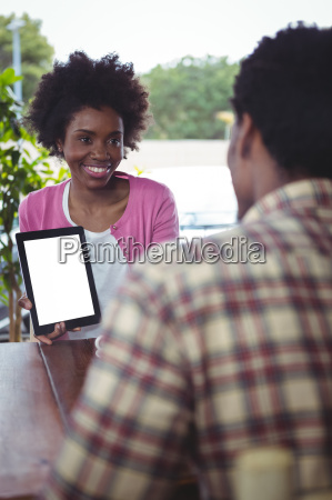 woman showing digital tablet to man