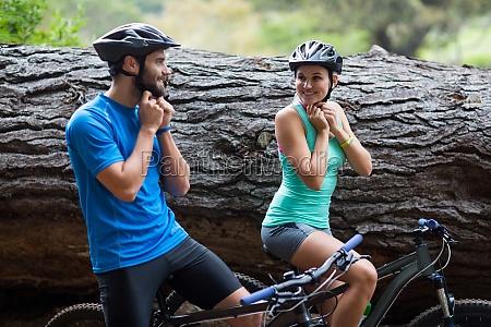 athletic couple wearing bicycle helmet