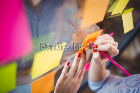 businesswoman writing on sticky notes stuck