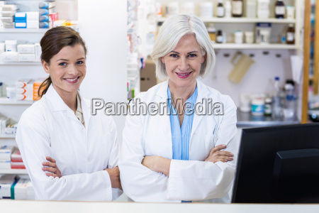 smiling pharmacists standing with arms crossed