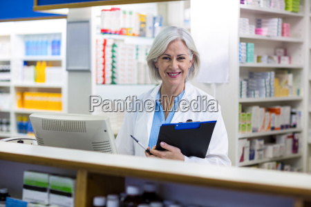 smiling pharmacist holding a clipboard in