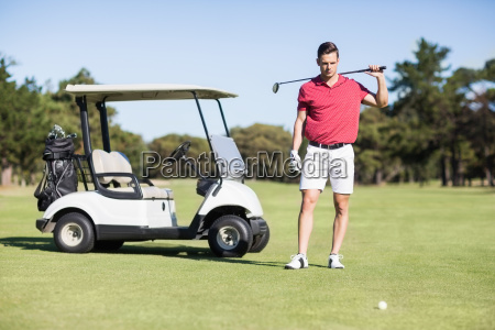handsome young man carrying golf club