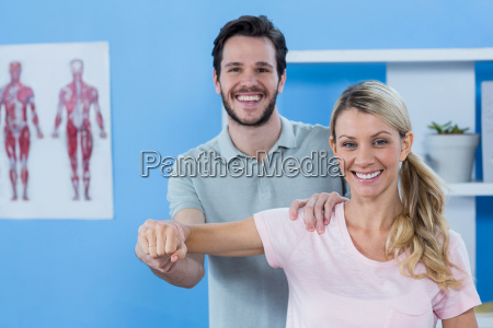 physiotherapist stretching arm of a female
