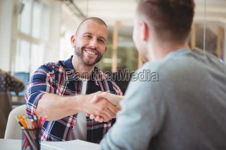 young business people shaking hands in