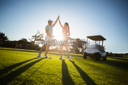 happy golf player couple giving high