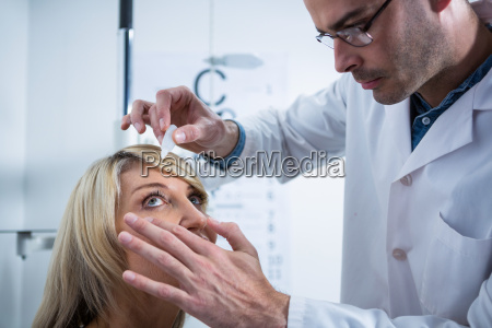 optometrist putting drops into patients eyes