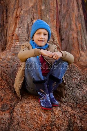 portrait of smiling boy hugging knees