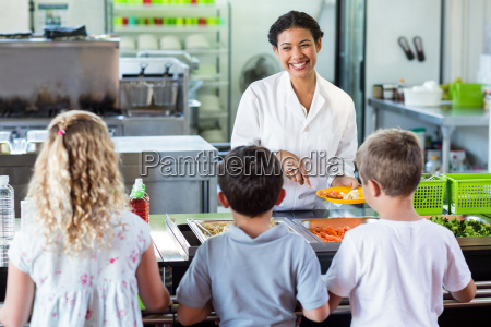cheerful woman serving food to schoolchildren