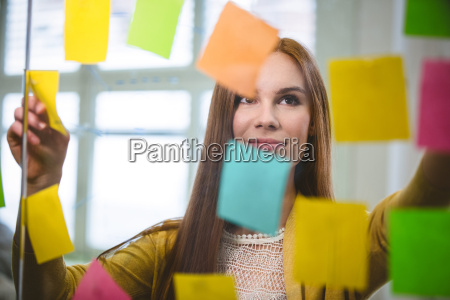 businesswoman looking at sticky notes on