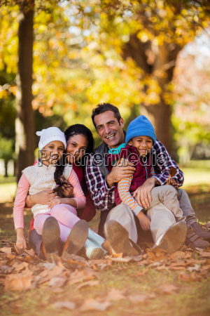 happy family sitting at park during