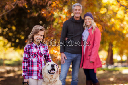 girl with dog while parents standing