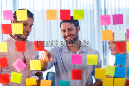 business people looking at post it