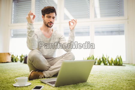 businessman doing yoga in front of