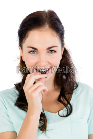 portrait of smiling woman eating chocolate